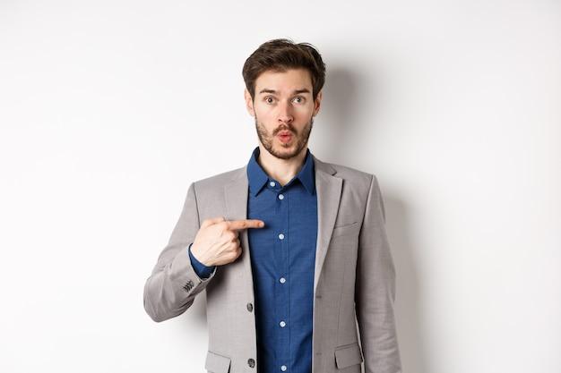 Кто я. удивленный мужчина в костюме, недоверчиво указывая на себя, смущенно глядя в камеру, стоя на белом фоне.