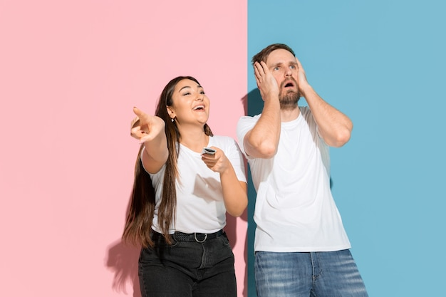 Who's in control. she chooses tv channel, he's angry. young man, woman in casual on pink, blue bicolored wall. concept of human emotions, facial expession, relations, ad. beautiful couple.