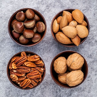 Whole almonds, walnuts ,hazelnut and pecan nuts in wooden bowl on stone background.