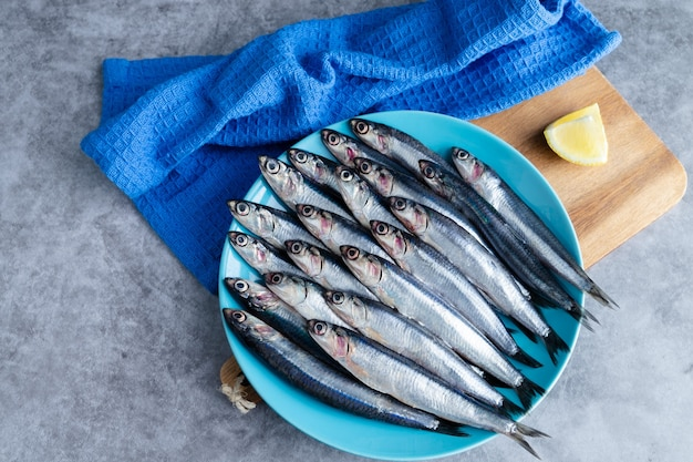Whole anchovies on blue plate on marble background. copy space. fresh fish concept. top view.