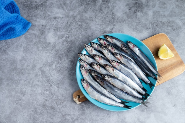 Whole anchovies on blue plate on marble background Premium Photo