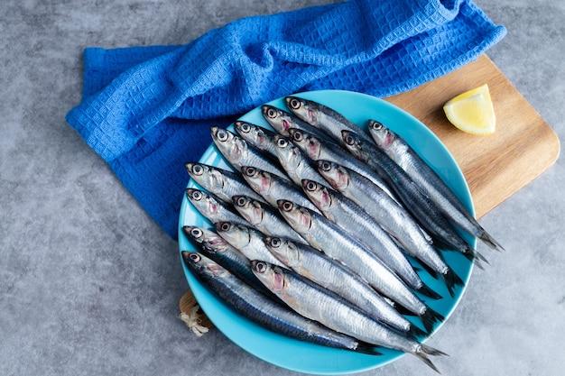 Целые анчоусы на голубой тарелке на мраморном фоне. скопируйте пространство. концепция свежей рыбы. вид сверху.