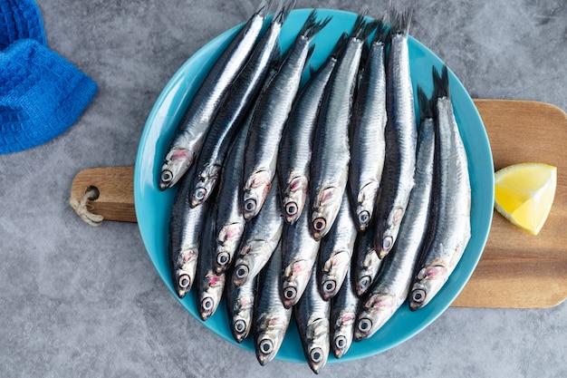 Целые анчоусы на синей тарелке на мраморном фоне