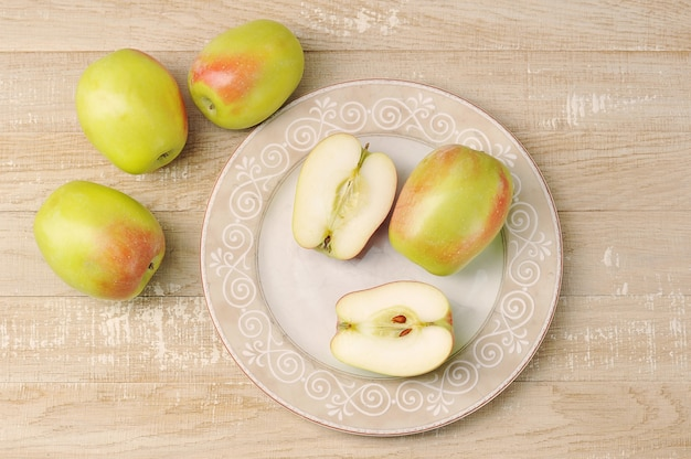 Целые и нарезанные яблоки на тарелке-осенний урожай яблок