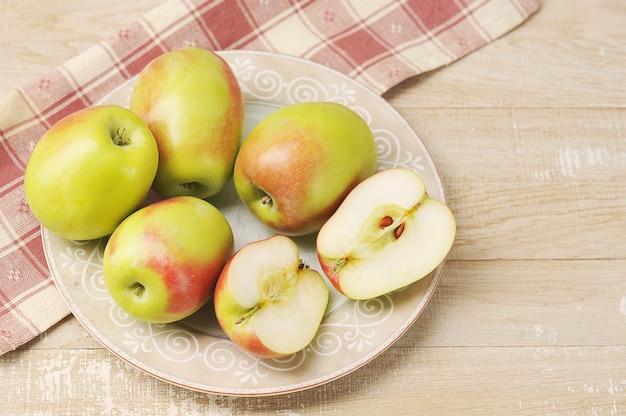 Целые и нарезанные яблоки на тарелке