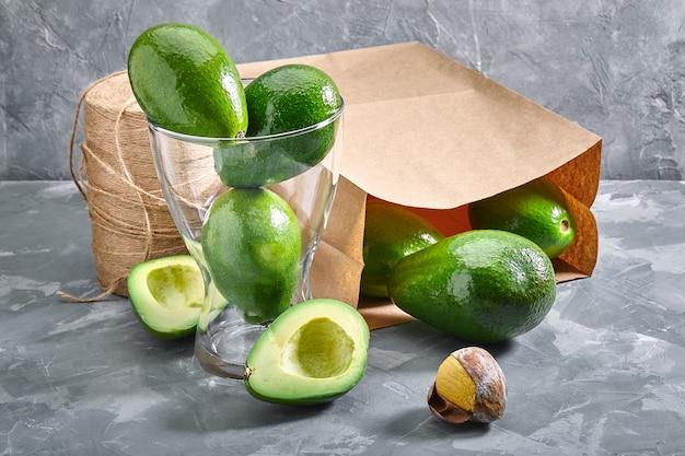 Цельные и нарезанные авокадо в вазе и лежащие на сером фоне из-за экологической упаковки. доставка продуктов, копии места, фотографии для каталога магазинов.