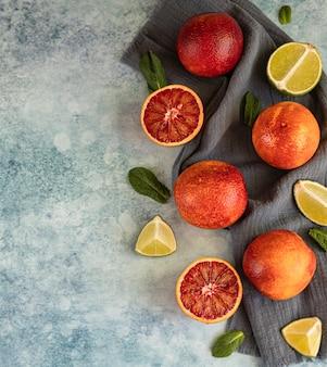 Целые и разрезанные пополам сицилийские апельсины, лаймы и мята вид сверху копирование пространства