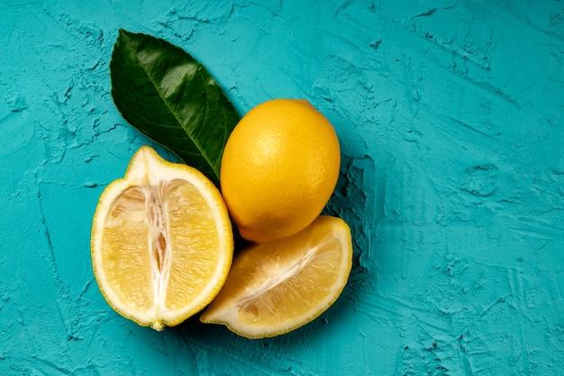 青い背景、食品の背景にレモン全体とカット。