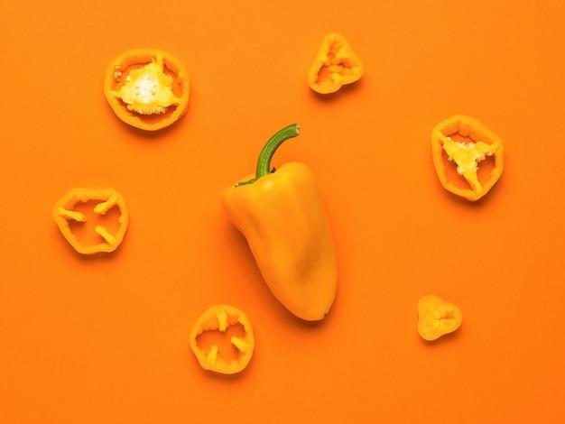 Целый и порезанный желтый болгарский перец на зеленом фоне. вегетарианская пища.