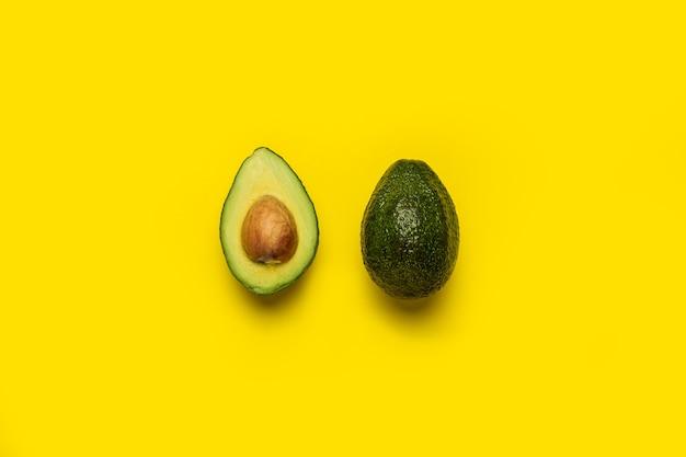 Целые и половинки авокадо на ярко-желтом