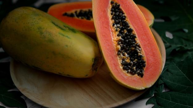 Целая и наполовину сладкая папайя на деревянной тарелке