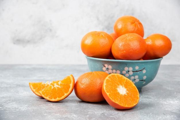 Сочные свежие апельсиновые плоды целиком и нарезать ломтиками в миске, стоящей на каменном столе.