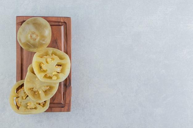 대리석 표면에 있는 나무 접시에 전체 및 슬라이스 토마토