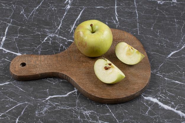 나무 보드에 전체 및 얇게 썬 사과입니다.