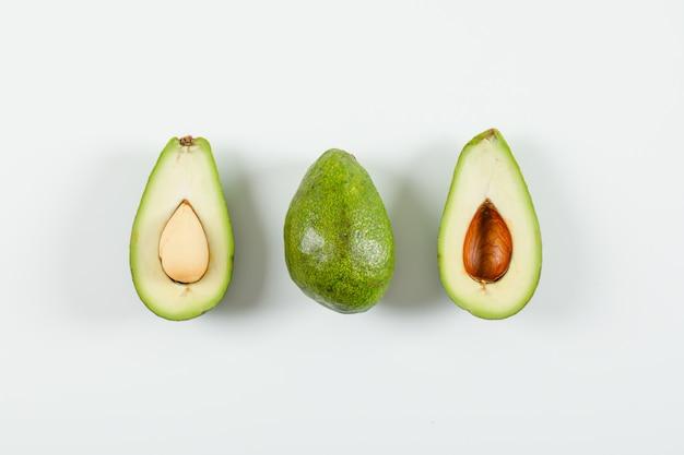 Целый и нарезанный авокадо на белой поверхности. вид сверху.