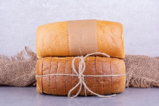 Целые и нарезанные блоки хлеба на мраморной поверхности