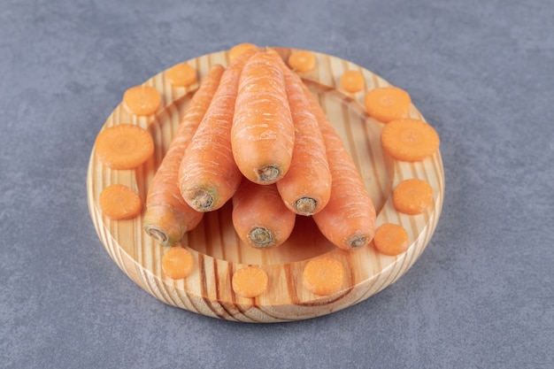 대리석 표면에 나무 접시에 전체 및 얇게 썬 당근.