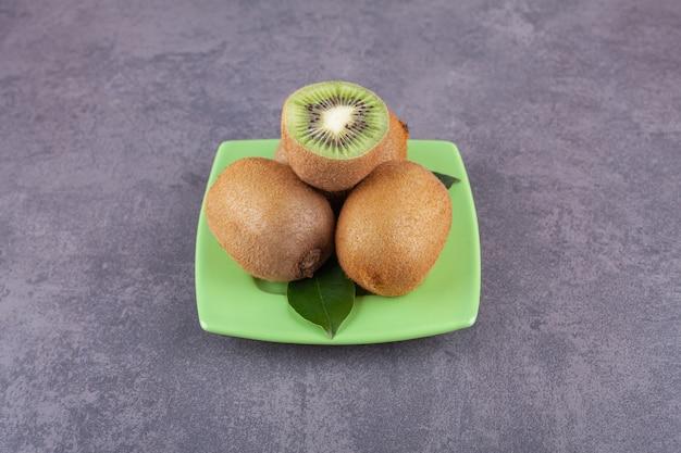 Целый и нарезанный вкусный киви с листьями на зеленой тарелке.