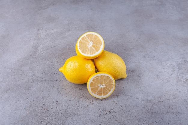 Целые и нарезанные свежие желтые лимоны на каменном фоне.