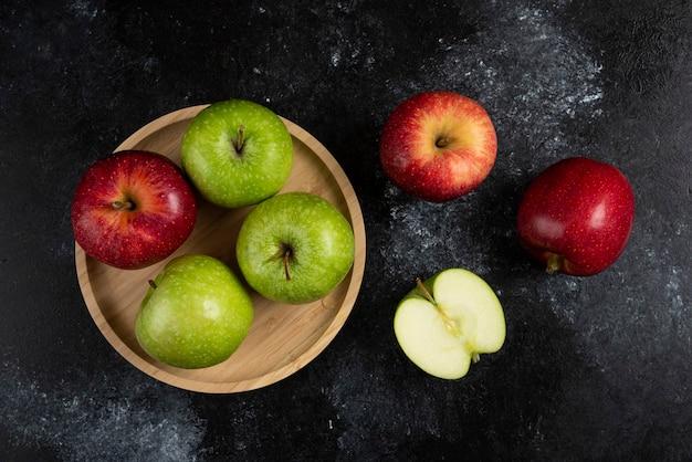 나무 접시에 전체 및 얇게 썬 녹색 및 빨강 사과.
