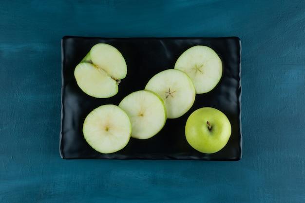 暗いトレイに置かれた丸ごとスライスされた青リンゴの果実。