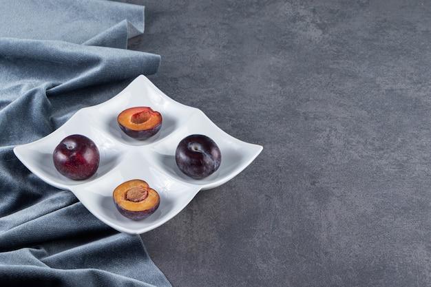 전체 및 얇게 썬 육즙이 붉은 매실 열매는 흰색 접시에 배치됩니다.