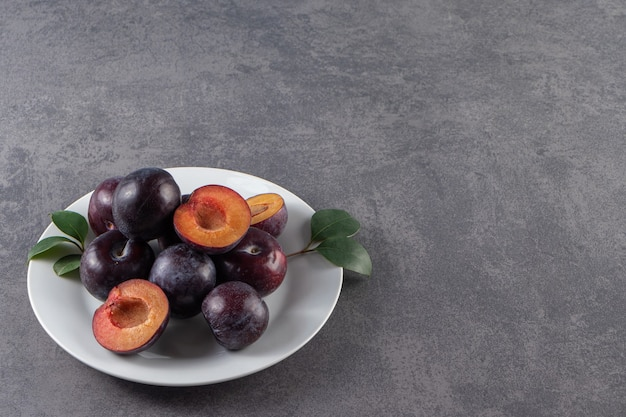 흰색 접시에 전체 및 얇게 썬 육즙이 붉은 매실 열매