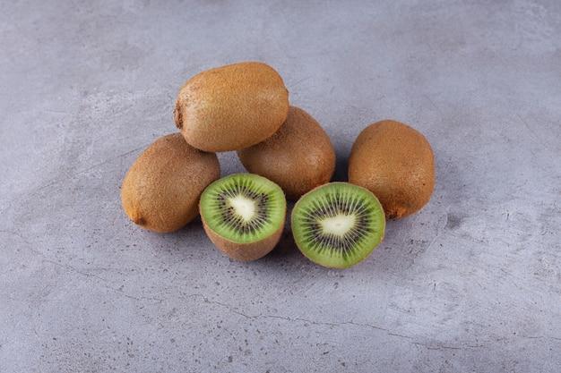 Целые и нарезанные плоды киви с листьями, помещенными на каменную поверхность.