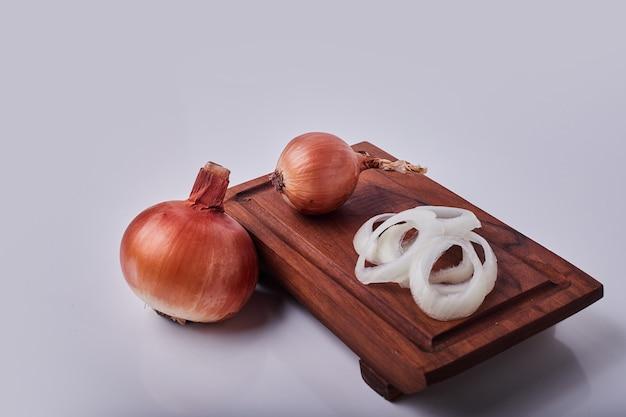 Целый и нарезанный лук на деревянной доске