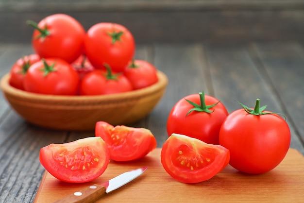 커팅 보드에 전체 및 얇게 썬 유기농 빨간 토마토.