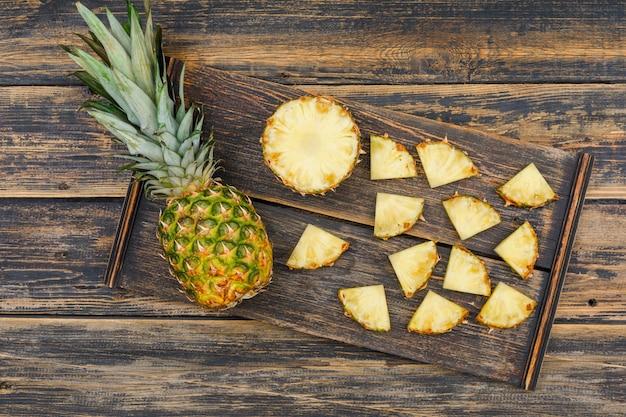 Весь и отрезанный ананас в деревянной части на старой деревянной поверхности grunge. плоская планировка