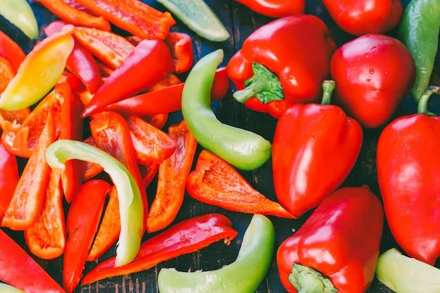 Целый и нарезанный красный и зеленый сладкий перец крупным планом