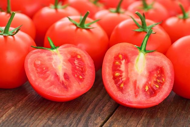 나무 테이블에 전체 및 얇게 썬 익은 토마토를 닫습니다.