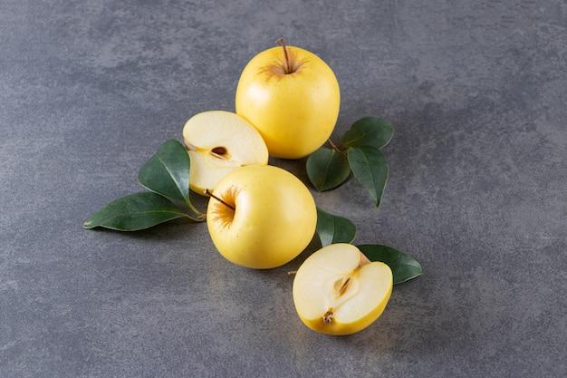 전체 및 얇게 썬 노란색 사과 과일은 돌 테이블에 배치됩니다.