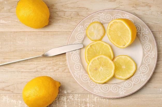 Целые и нарезанные желтые лимоны на тарелке на деревянном