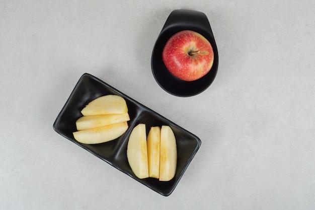 Целое и кусочки красного яблока на черных тарелках.