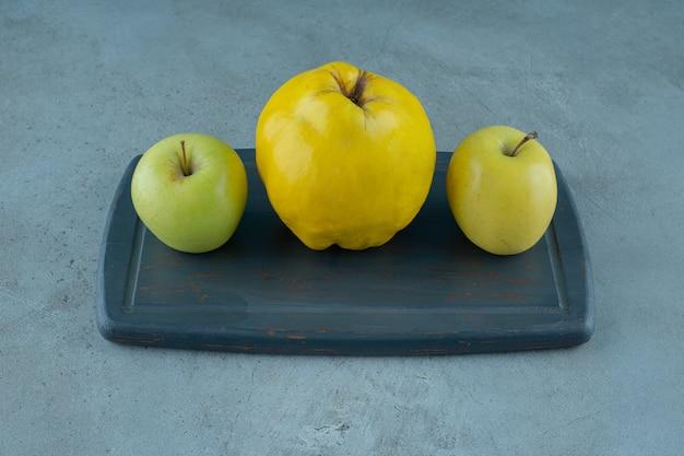 Целые яблоки и айва на доске, на мраморном фоне. фото высокого качества