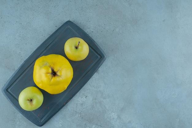 大理石の背景に、ボード上のリンゴとマルメロ全体。高品質の写真