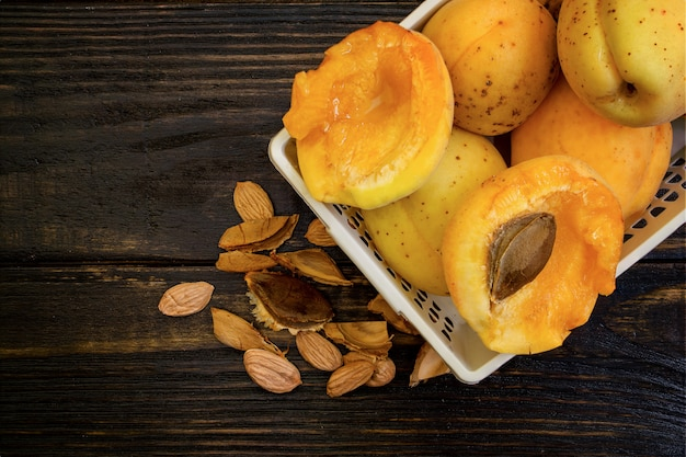 Whole apricots and halves in a basket, on a wooden table with broken apricot pits,