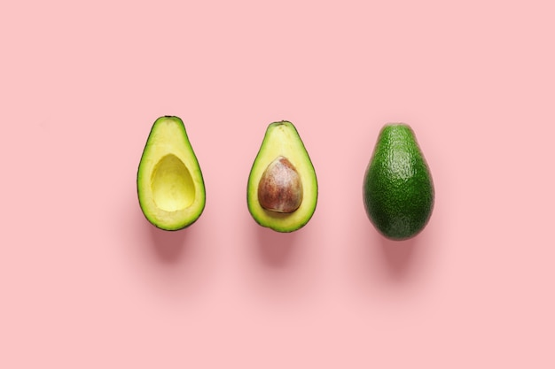 Whole avocado fruit and two halves in a row isolated on pink background.