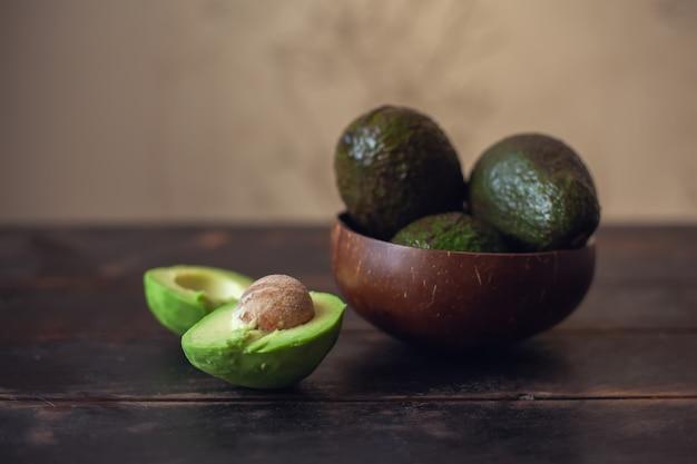 ココナッツの殻で作られたボウルにアボカドの果実全体が半分にカットされ、暗い木製の背景にその隣にあります。