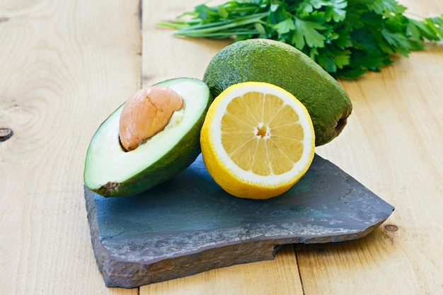 Whole avocado and lemon, parsley or cilantro on a stone board