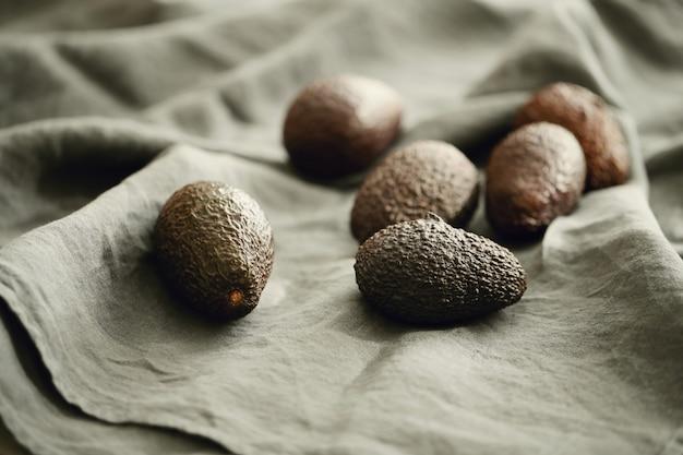 Целые авокадо на серой ткани