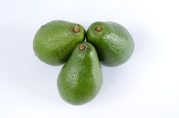 Целые авокадо на белой поверхности