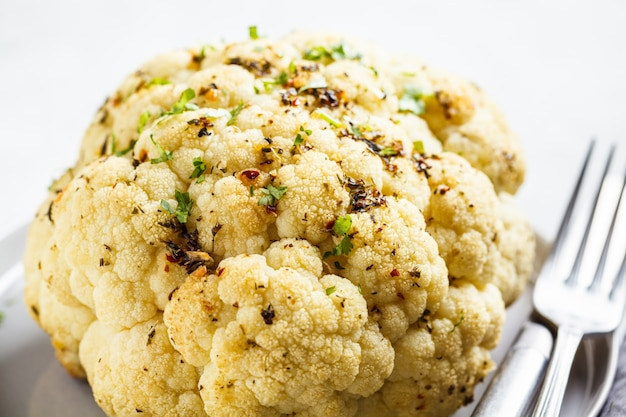 Whole baked cauliflower with spices on gray plate. healthy vegan food concept.