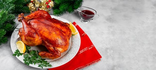 プレートにパプリカとクリスマステーブルの設定、テキスト用のコピースペースのあるウェブサイトのバナーを添えたソースで焼いたチキンまたはターキー全体。高品質の写真