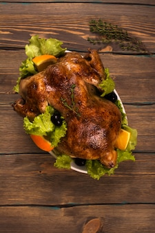 Whole baked chicken with garnish over wooden background. holidays food. rustic style