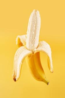 Целый банан с кожурой, изолированные на желтом