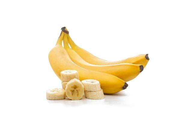 Целые бананы и ломтики, изолированные на белом фоне