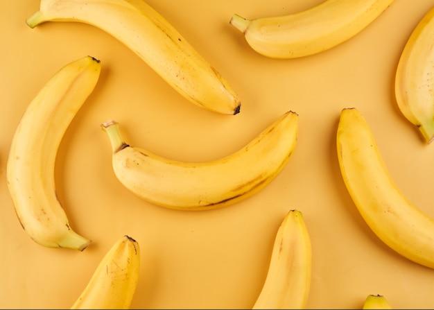 黄色の背景、果物の壁紙に皮のパターンを持つバナナ全体